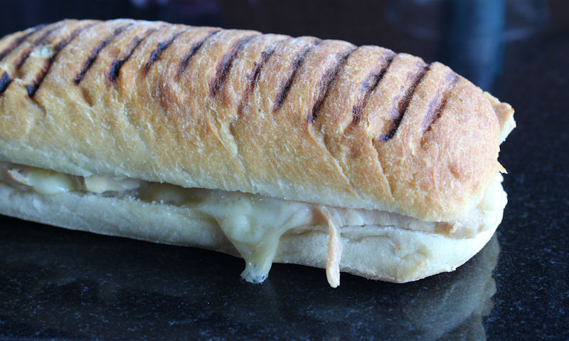 Cooked panini with melted Cheddar cheese