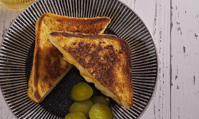 Serving of sliced pickles with grilled cheese sandwich