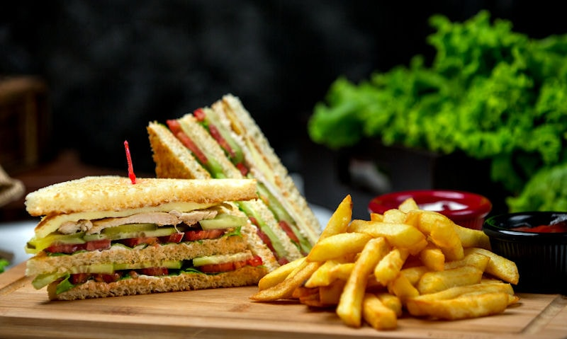 Chicken, avocado sandwich served with french fries