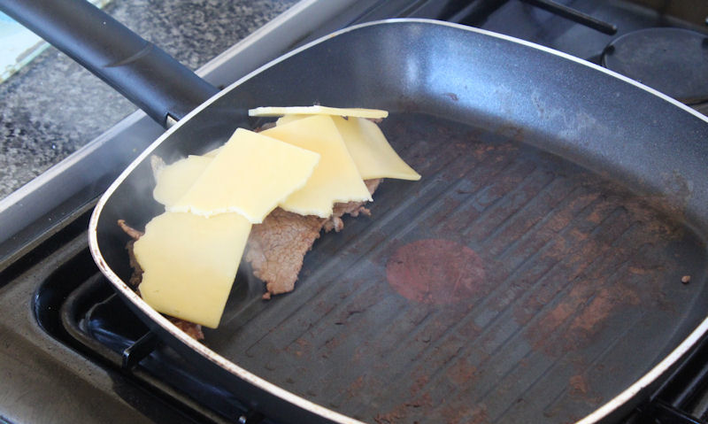 Melting cheese on beef strips in pan