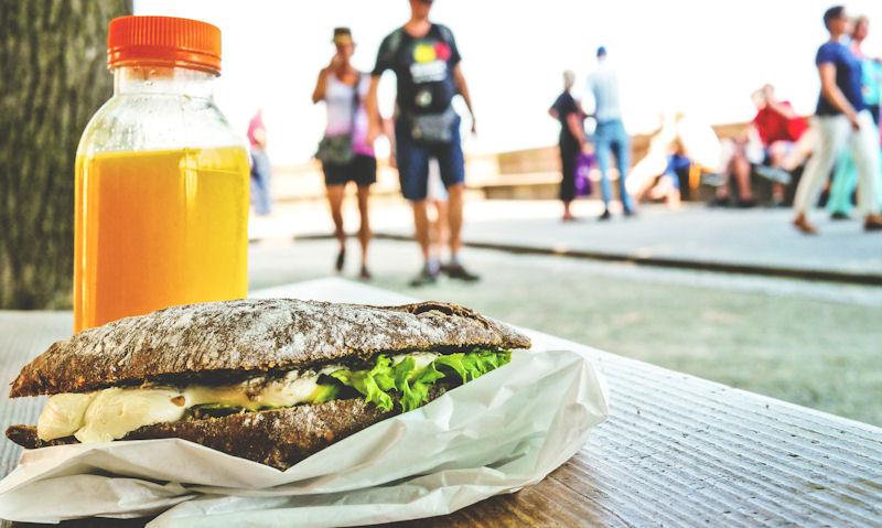 Bottle of orange juice served with gourmet sandwich